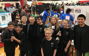 5th grade students on the First Lego League team pose for a picture before going to their project presentation at the Mount Prospect Regional tournament on December 14th. They are wearing black t-shirts with Sullivan robotics.