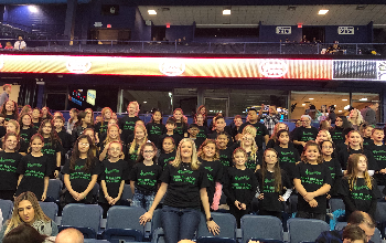 Sullivan chorus students and Mrs. Luehr posing for a picture in the rows of chairs at the wolves game.  They are wearing their black and green chorus shirts.