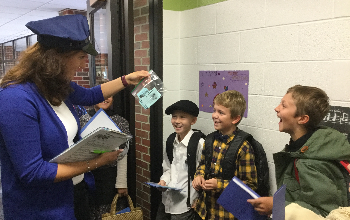 Three boys from 4th grade are being questioned about their money by a fake police officer at our Ellis Island simulation. The fake police officers is holding up a bag full of blue money and students are smiling at her.