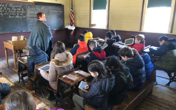 Fifth grade students are sitting in a one room schoolhouse at Naper Settlement. Students have been learning about colonial times and they took this trip to experience what it was like when colonists arrived in America. Students are writing on black slate