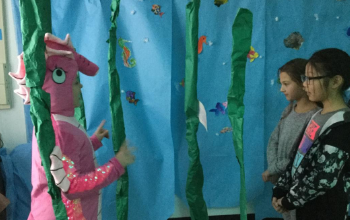 Student in Mrs. Broms' class dressed up as a seahorse standing near hanging seagrass made out of green paper. The background is blue paper hung up with colored fish on the paper. Two girl students are listening to the student dressed as a seahorse (pink s