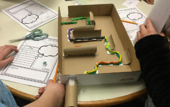 Picture of a cardboard box marble maze that uses clay, toilet paper rolls and other materials to move a marble around a self-made track.