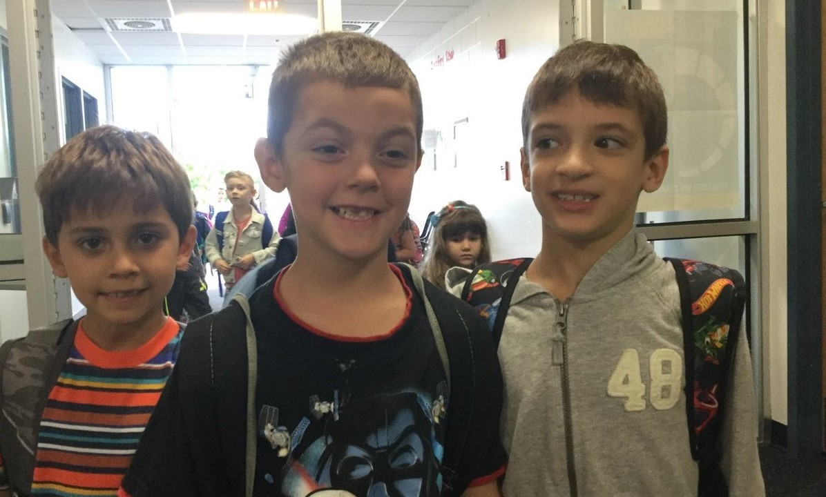 Three boys smiling for a pictures