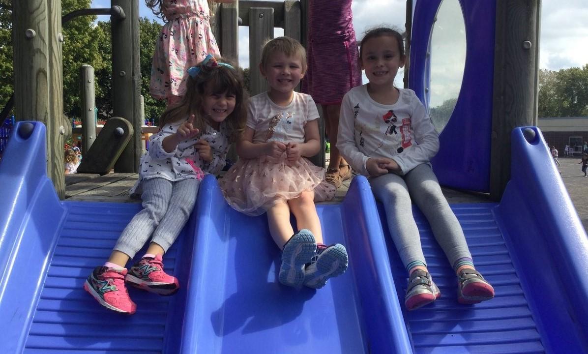 Three girls going down the slide