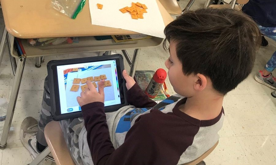 A Boy using his iPad to calculate his cheese its.