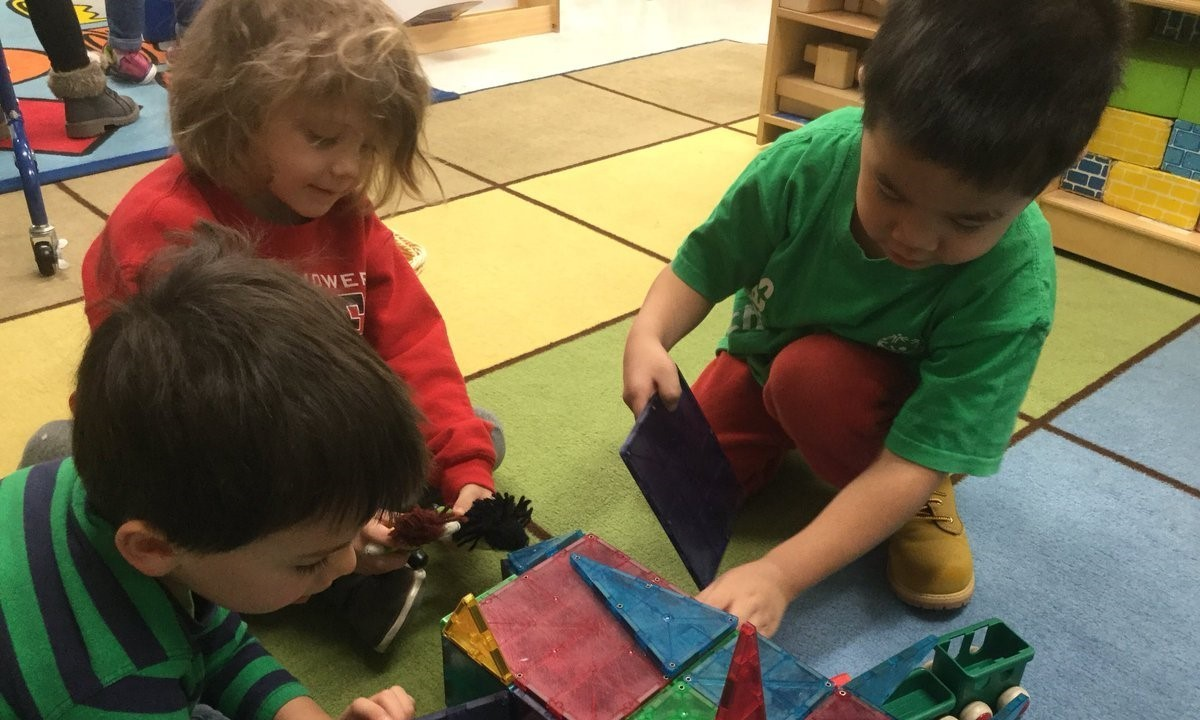 Students working together to build using shape tiles