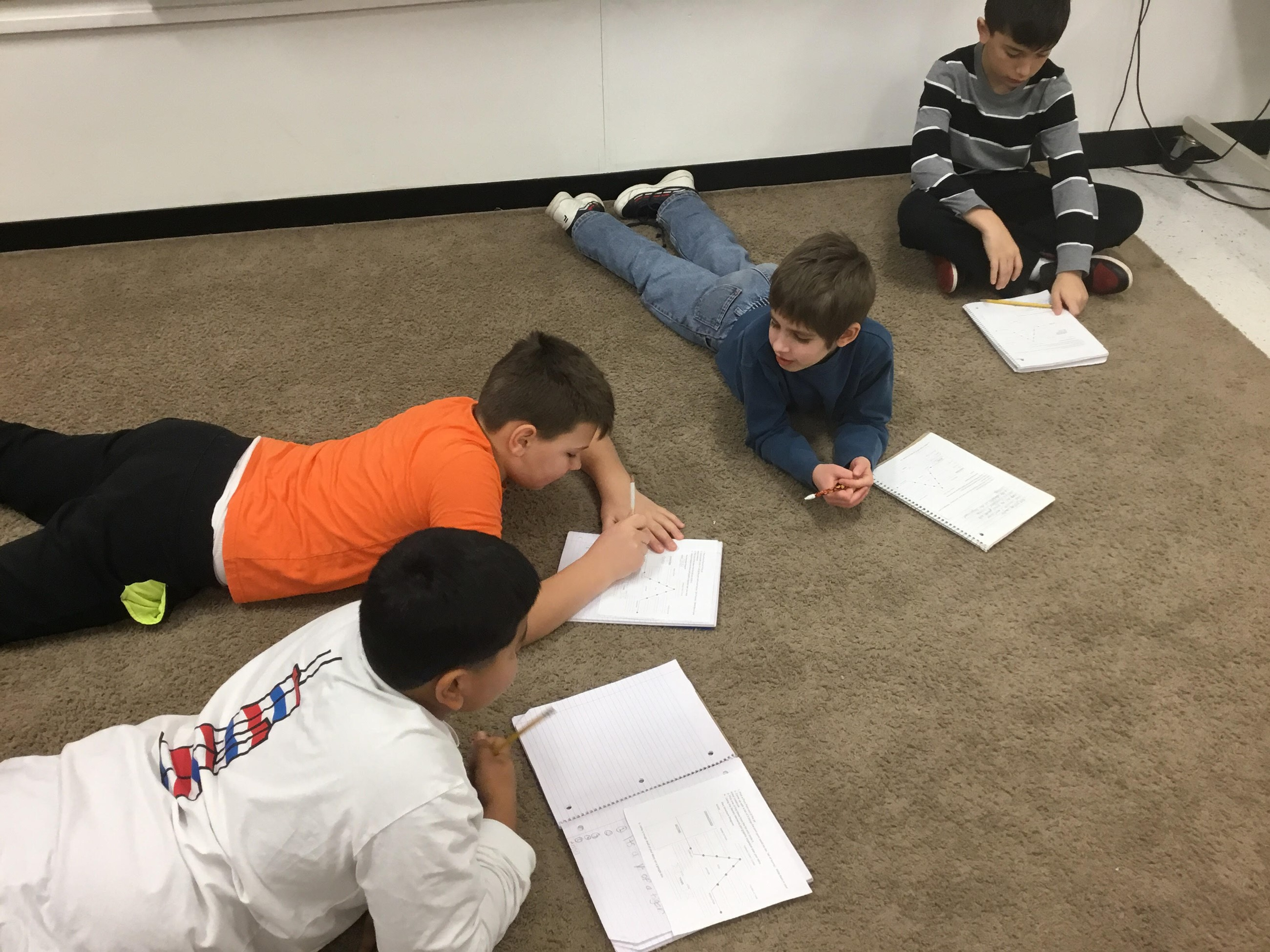 Mrs. Brusso's 4th grade class writing on the carpet area in their notebooks.