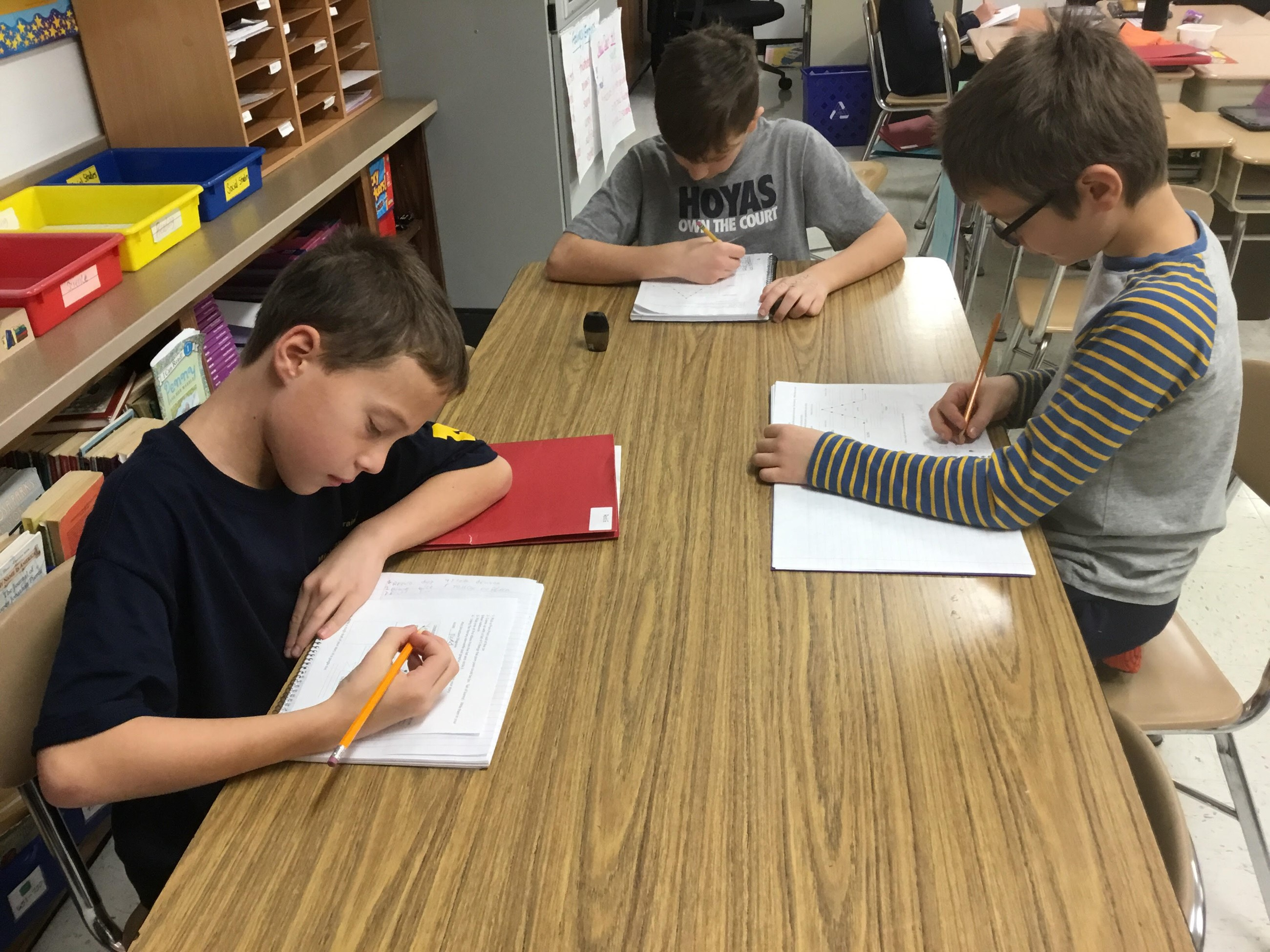 Mrs. Brusso's 4th Grade class group of boys writing at a rectangular table.