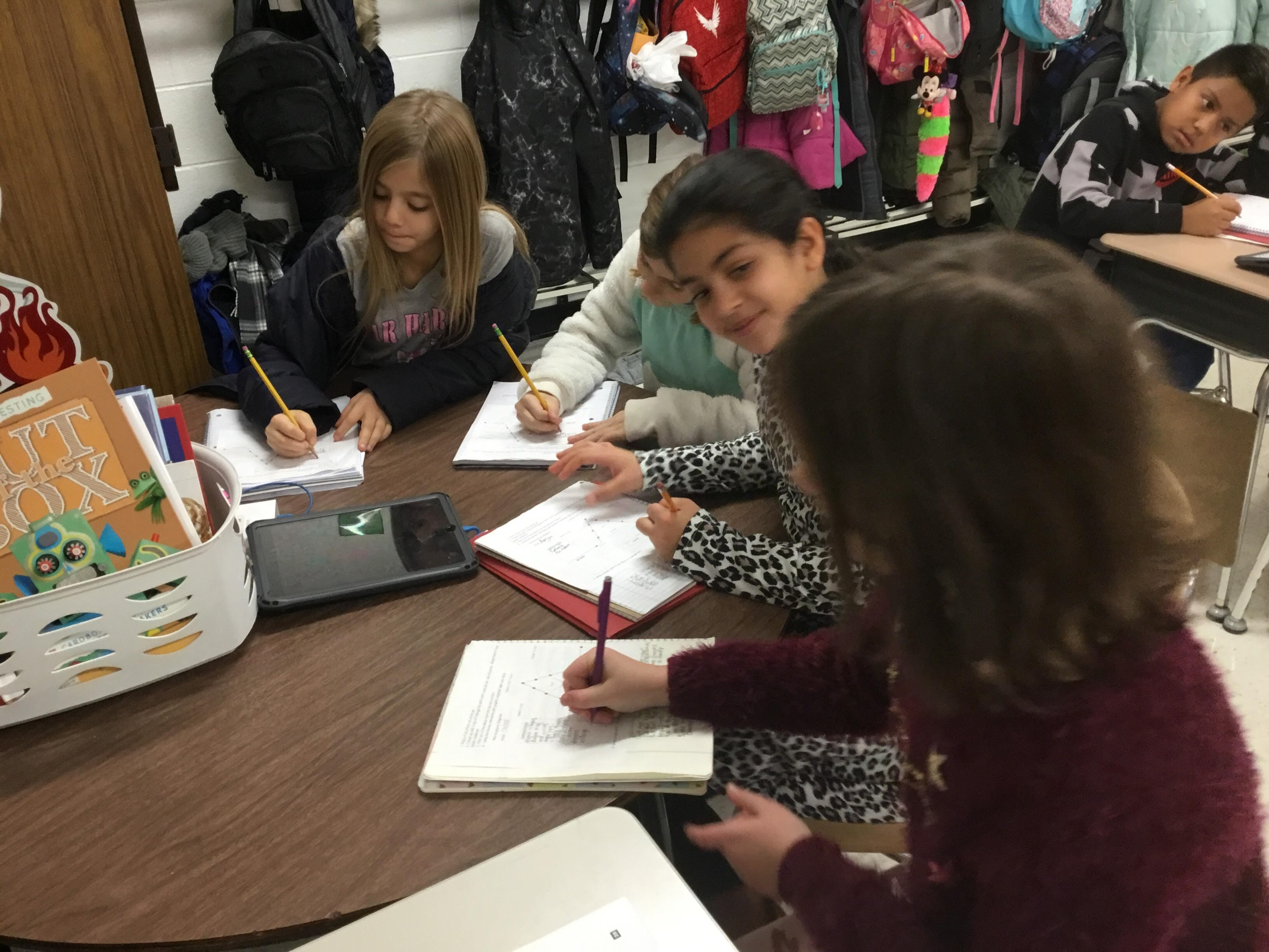 Mrs. Brusso's 4th Grade Class writing in their notebooks. A group of girls are sitting at a table together writing.