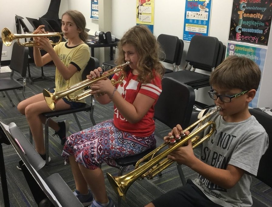 Three students playing the trumpt