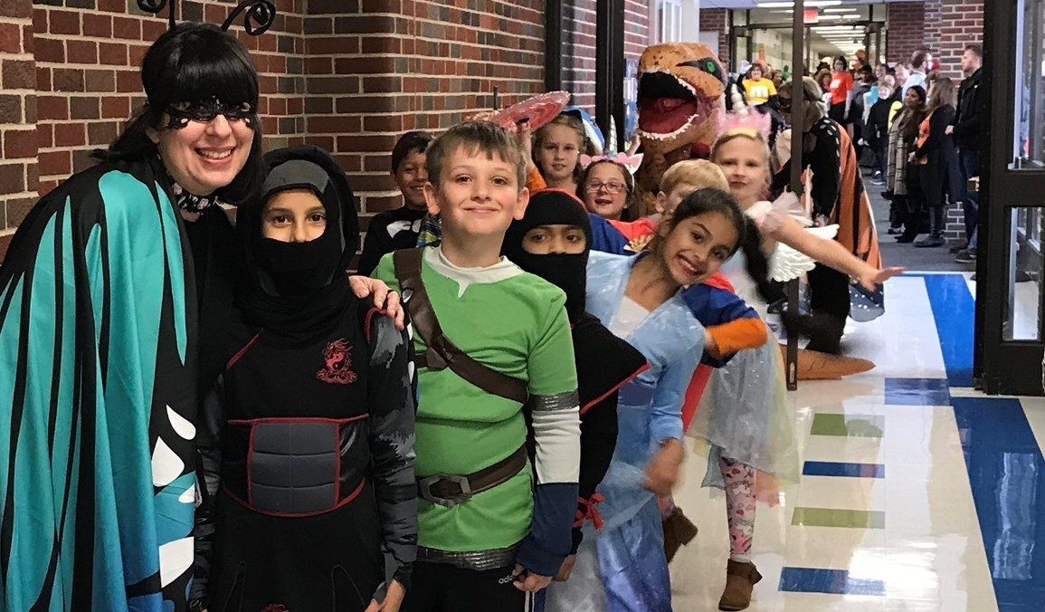 Students with teacher in the hallway dressed in costumes for Halloween and parade.