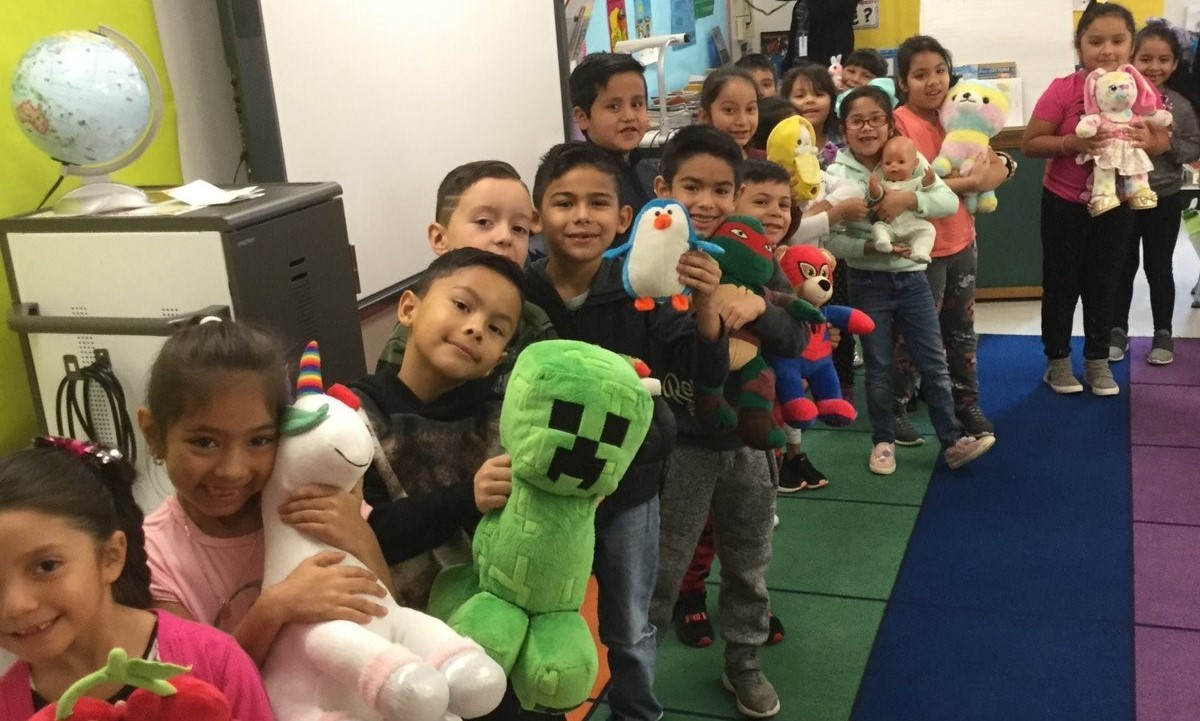 Students showing their plush toys
