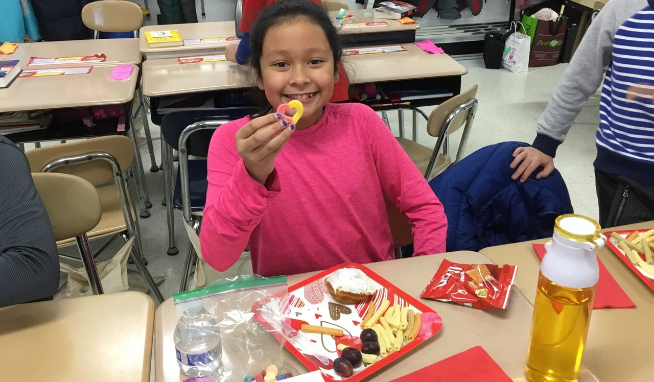 Student in Mrs. Ganek's class sharing her cupcake decorations for the Valentine's Day celebrations.