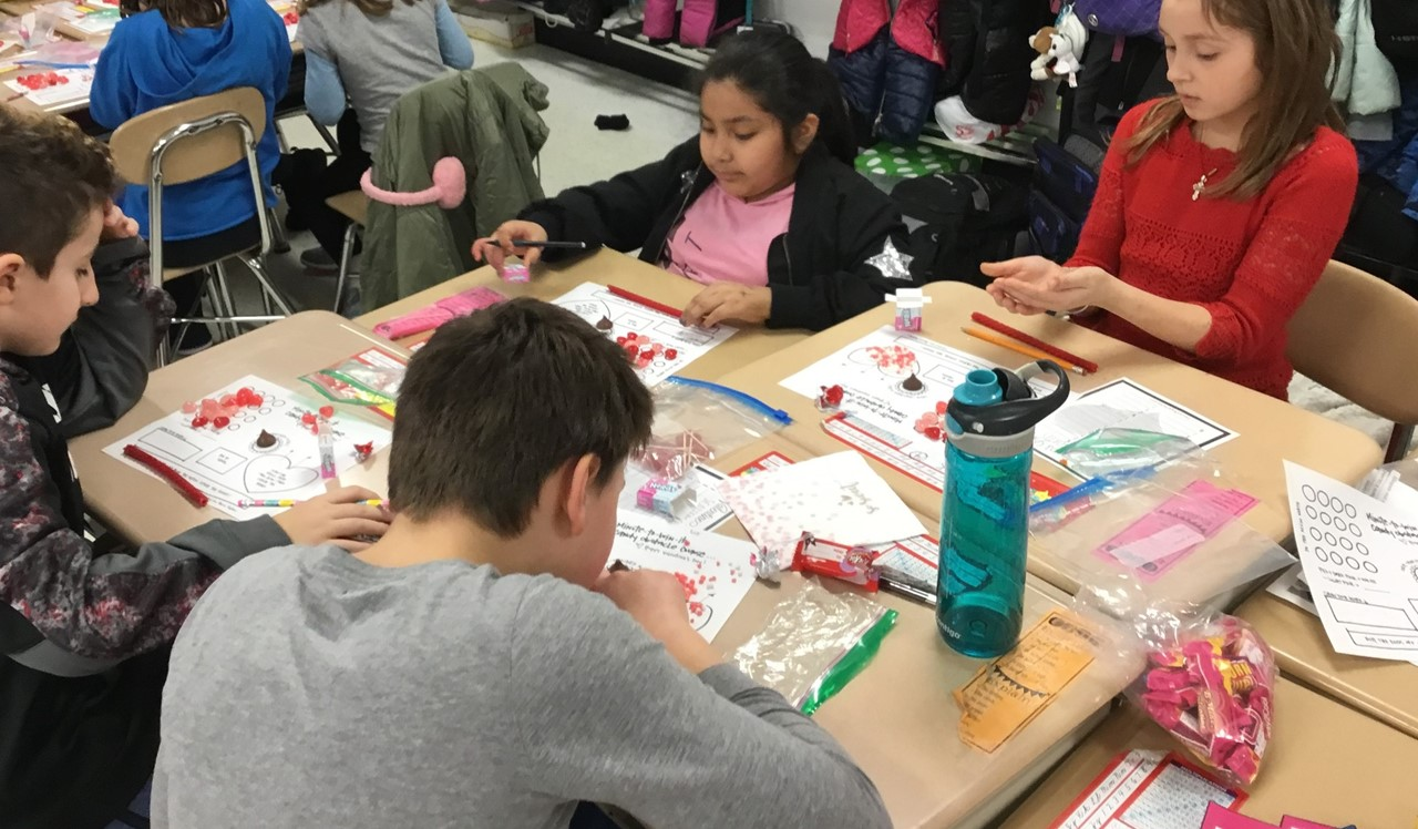 Students in Mrs. Brusso's classroom doing a Valentine's Day activity with their group.