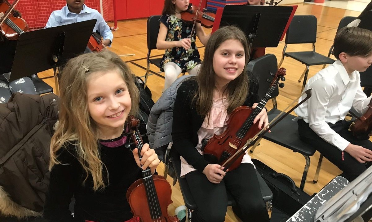Two girls with their violins smiling