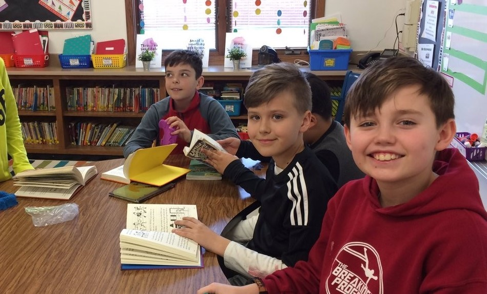 Boys smiling as they read their books