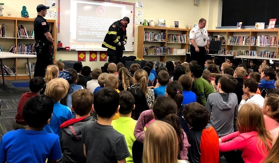 Firefighters talking to second grade students