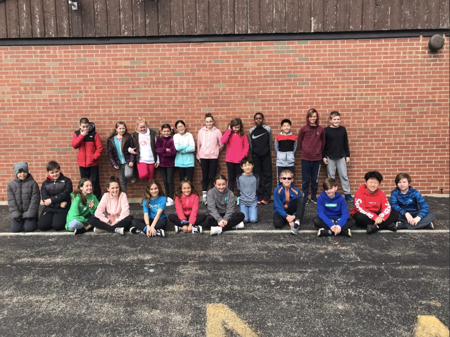 Ms. Wessel's 5th grade class group picture outside with a brick background from the side of the school.