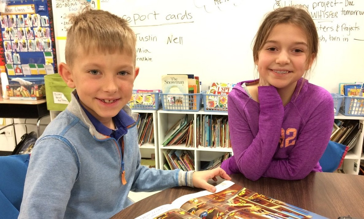 boy and a girl are smiling and reading a book