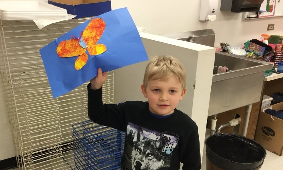 boy holding up his art work of a butterfly