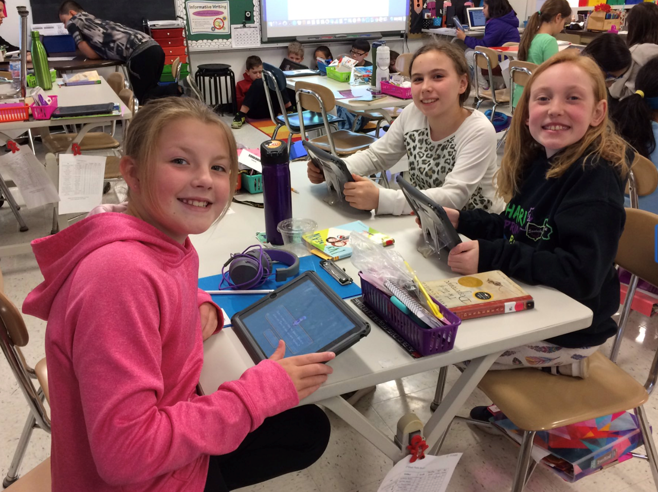 Three girls smiling while working on their iPads.