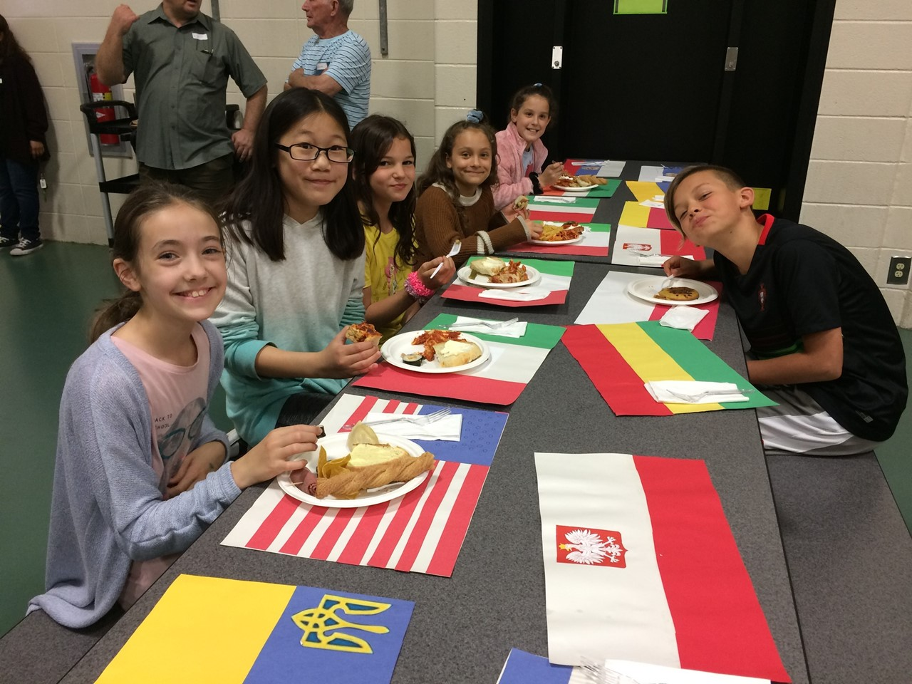 Heritage Day for 5th graders end of project culminating celebration. Students share their autobiographies and about their culture. They bring in food from their different cultures to share with others in 5th grade.  In this picture, students are sitting at a lunch table eating with placemats that look like flags from different countries.