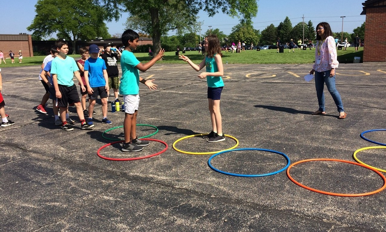 Field day activity with students competing in a relay race where if they meet in the middle of the race track (hula hoops) they play rock, paper, scissors to see who goes first.