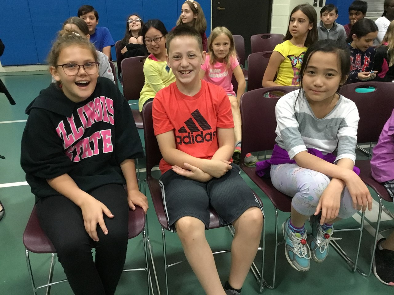 Students in the end of the year spelling bee. They are sitting in chairs ready to start the spelling bee.