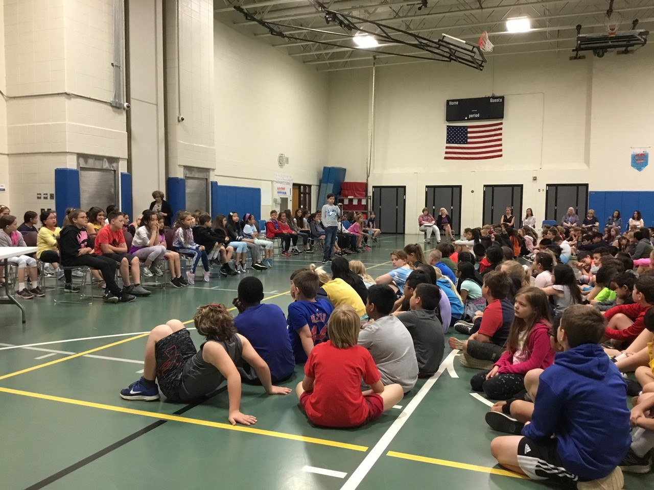 End of the year spelling bee assembly. Students are sitting on the floor in the gym and students (contestants) are sitting in chairs preparing to spell in the spelling bee.