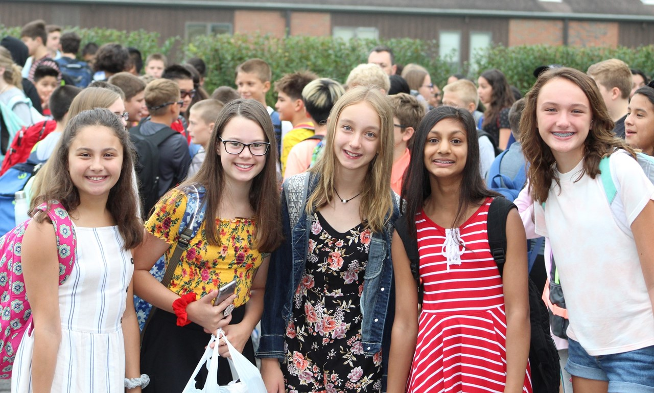 Five girls smiling on the first day of school