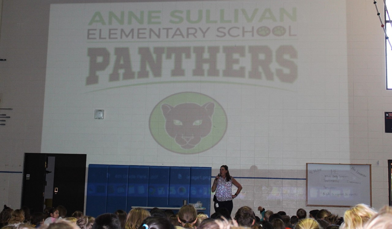 Mrs. Meziere, our principal at Anne Sullivan, is introducing our new school mascot! We are now the panthers and our school colors are black and green.