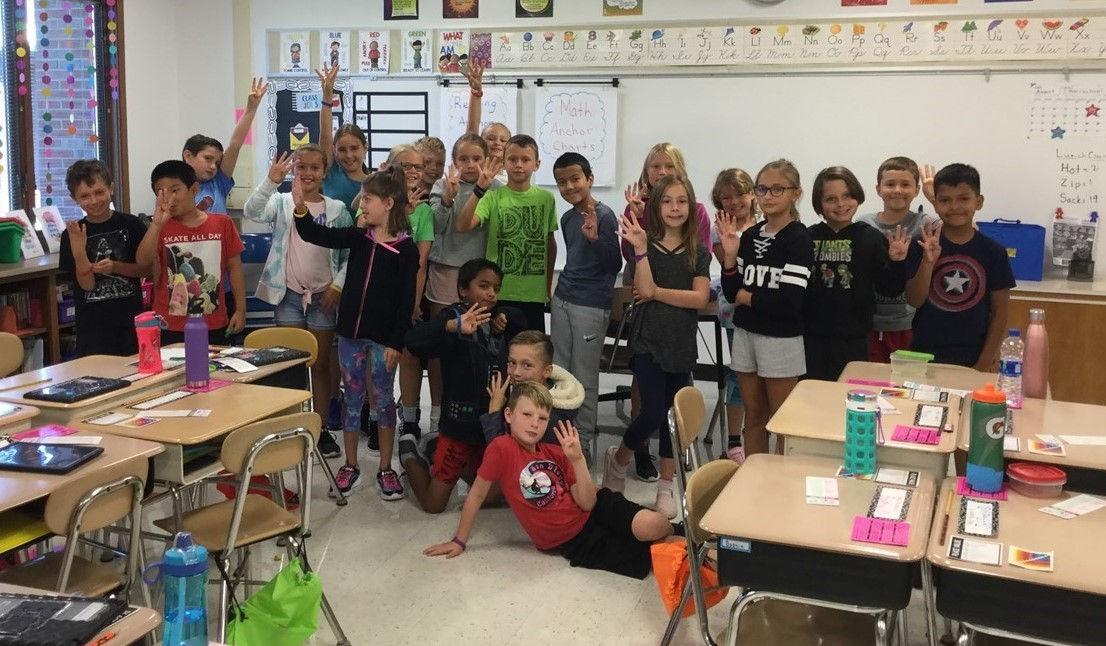 Picture of Mrs. Ganek's 4th grade class, whole group picture, holding up 4 fingers indicating they are in 4th grade.