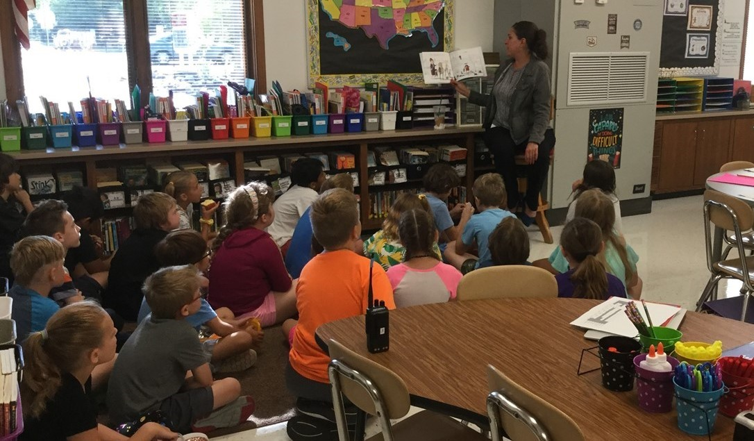 Mrs. Meziere is reading a book to a 5th grade class during the first week of the 2019-2020 school year. Students are sitting on the rug (on the floor) and Mrs. Meziere is sitting in a chair in front of them.