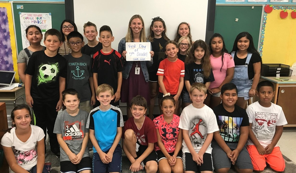 Ms. Wessel's 5th grade class, whole group picture taken on the first day of school. Ms. Wessel is holding a small whiteboard that says First Day of 5th grade 2019-2020.