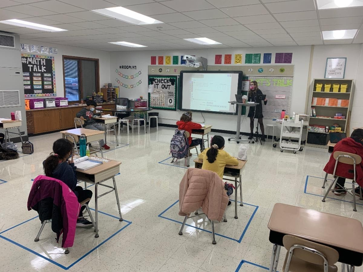 4th graders in Ms. Slowik class are in class for the first time during our hybrid instruction. Ms. Slowik stands at the front of the room teaching to students in their desks. The desks are placed in taped off areas on the floor to keep and maintain social distance. Students all wear masks.