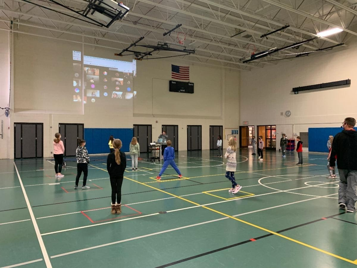 PE classes are online and in person with hybrid instruction. Students are in the gym watching a video for instruction on the upper screen. Mr. Miller is in the foreground instructing students. Students are in socially distanced boxes taped on the floor.