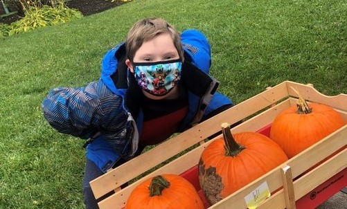 Boy with mask over three pumpkins in a wagon