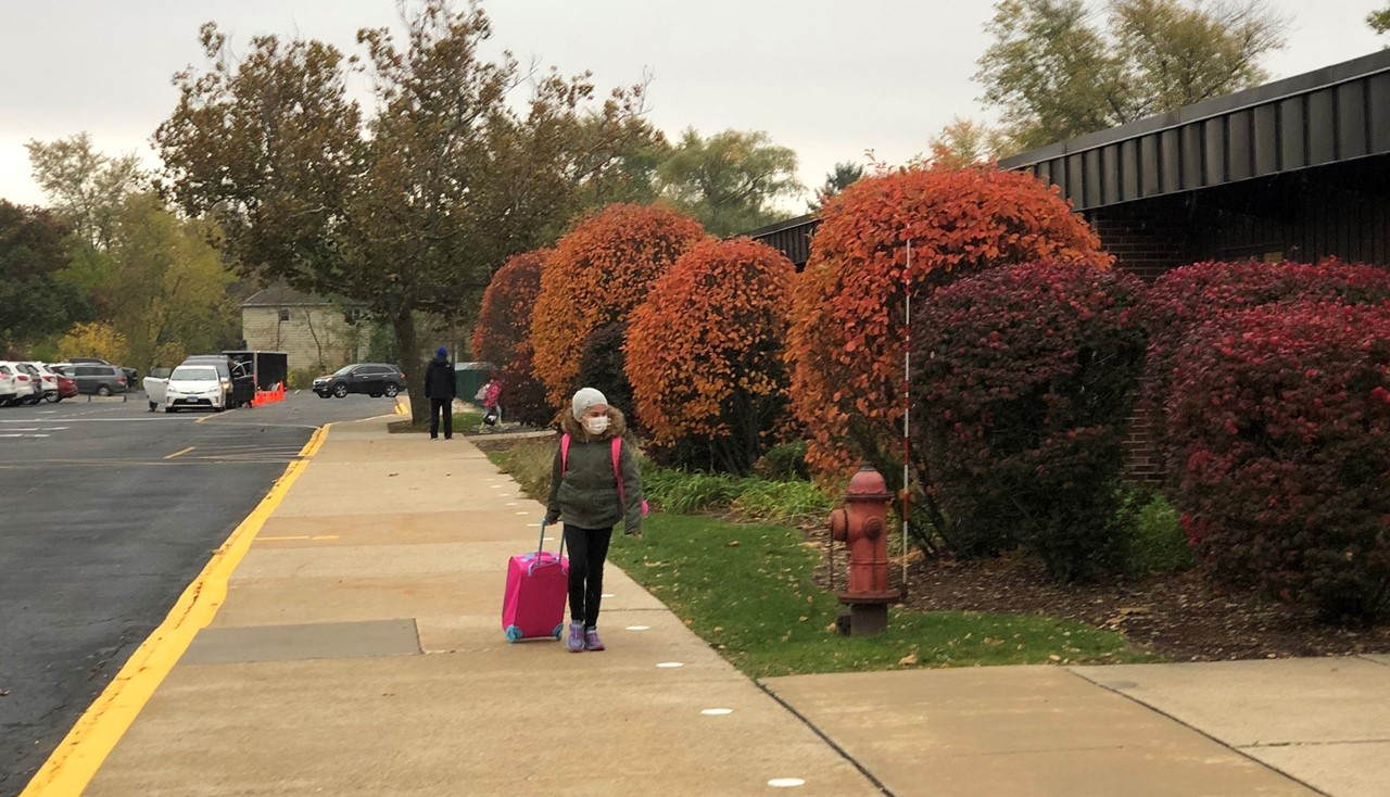 A girl in a mask and jacket pulling her carry on to school for the first time this year.