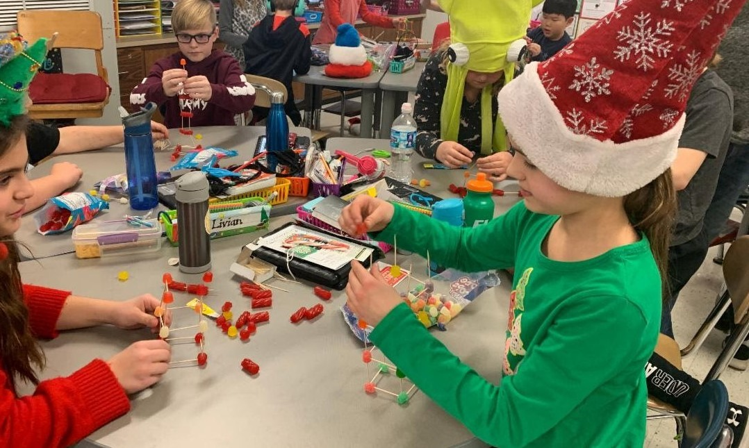 Students are dressed in holiday hats and sweaters. They are building tall towers out of toothpicks and gumdrops during their holiday party before Winter Break.