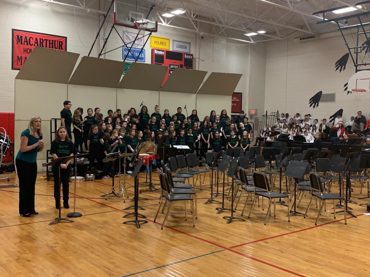 This picture shows our chorus performing at the Winter concerts. They are standing on risers in rows. One students is at the microphone and Mrs. Luehr the chorus director is standing next to her addressing the audience.