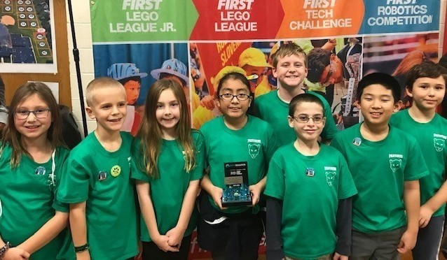 "4th grade students from the Lego League team, the Colossal Coders, are holding their trophy from the Mount Prospect Regional tournament on December 14th. They won the ""Rising Star"" award. The students are wearing their green Lego League shirts and standing as a group. They are standing in front of a First Lego League backdrop."