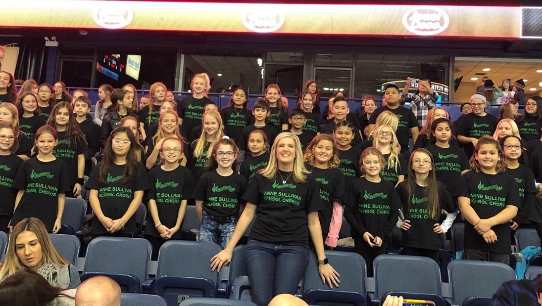 Mrs. Luehr and the Sullivan chorus pose for a picture at the Wolves game. The group went to the Wolves game to perform songs and watch the game together. The group is wearing their black shirts with green lettering.