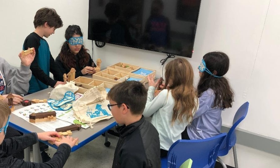Students in Mrs. Travis' class use empathy tools to learn about communication with others. Some students in the picture are wearing blindfolds and the student who is not blindfolded is explaining how to build specific design. Eight students are sitting around the table in pairs.