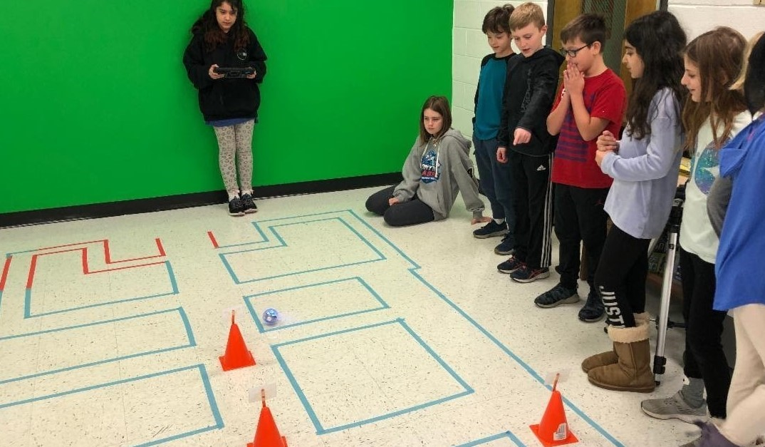 Students in Mrs. Travis' class use mazes with spheros robots to test out their skills. Students are lined up along the side of the maze and one student is using an iPad to navigate through the maze. She is standing at the start of the maze area.