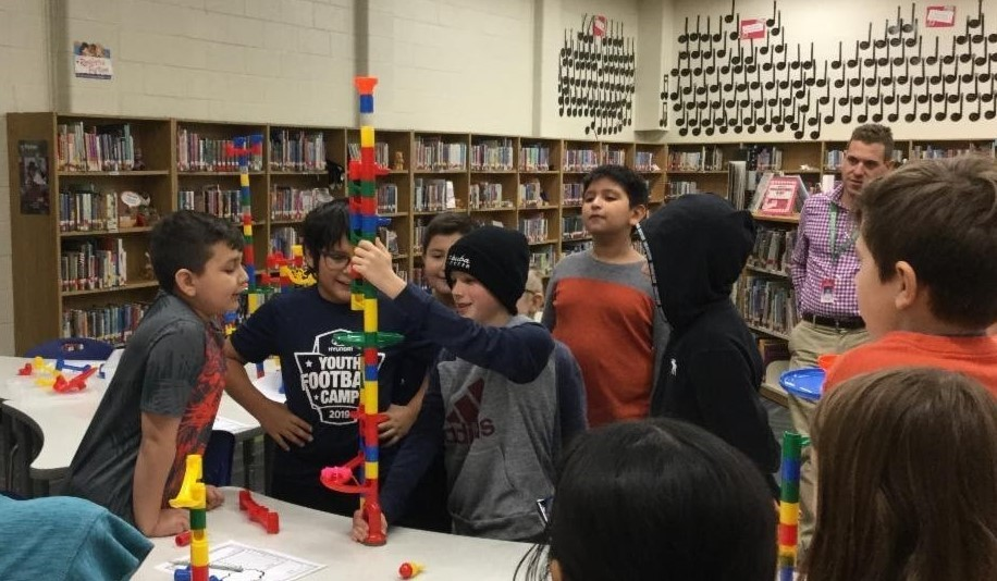 Students in the Sullivan STEAM club are building tall towers out of marble maze materials. Students also built marble mazes out of cardboard boxes and other materials. Students are standing around one table. A few students are standing and holding a tall table holding their tower.