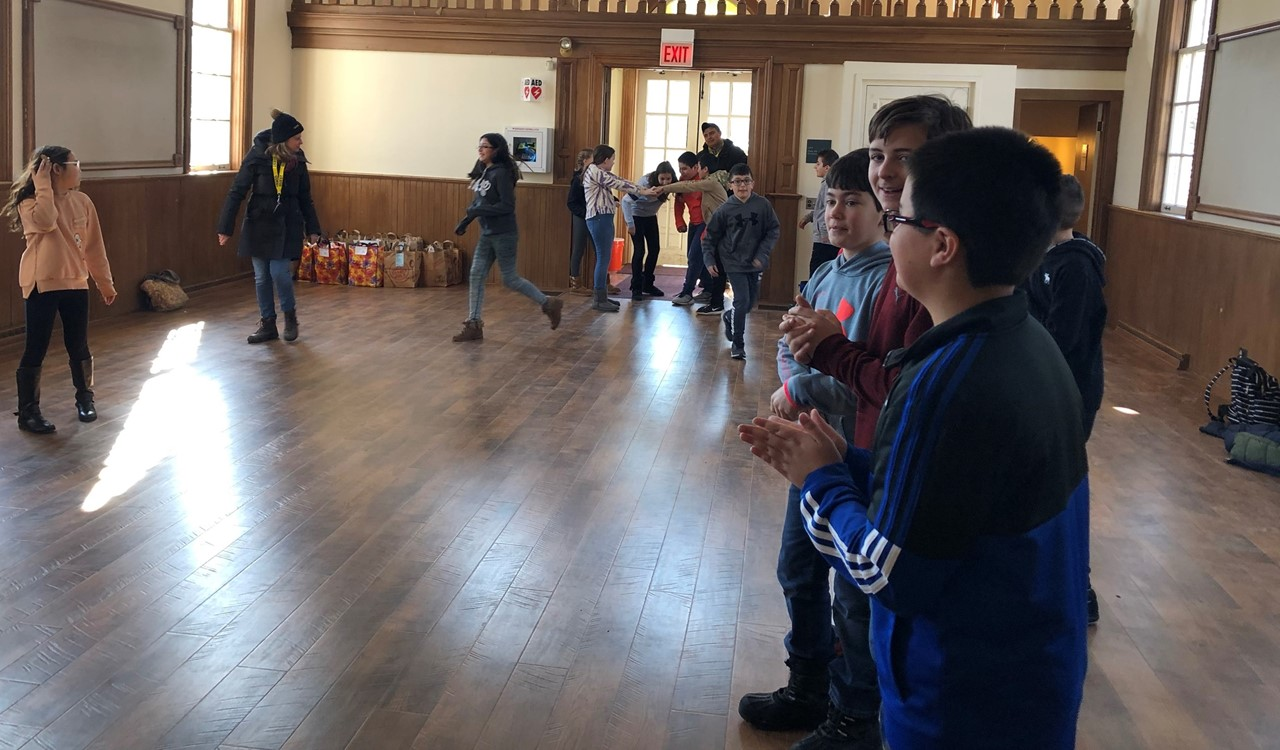 Students in 5th grade are on a field trip to Naper Settlement. The students are in a large room. Boys are lined up on one side and girls are starting to line up on the other side. They are going to be learning about dances from colonial times on their field trip to Naper settlement. The room has wood floors and a wooden balcony area too.