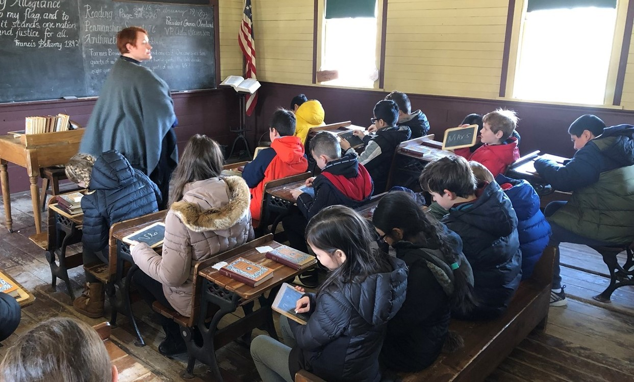 Students from 5th grade classes at Sullivan went on a field trip to naper settlement to see what it was like in early colonies for school, work, chores and more. This picture shows students being taught in a old school house with wooden desks and benches. They are writing on black slates with chalk and at the front of the room a presenter is pretending to be their teacher. They are using this opportunity to experience how people lived in early colonies.