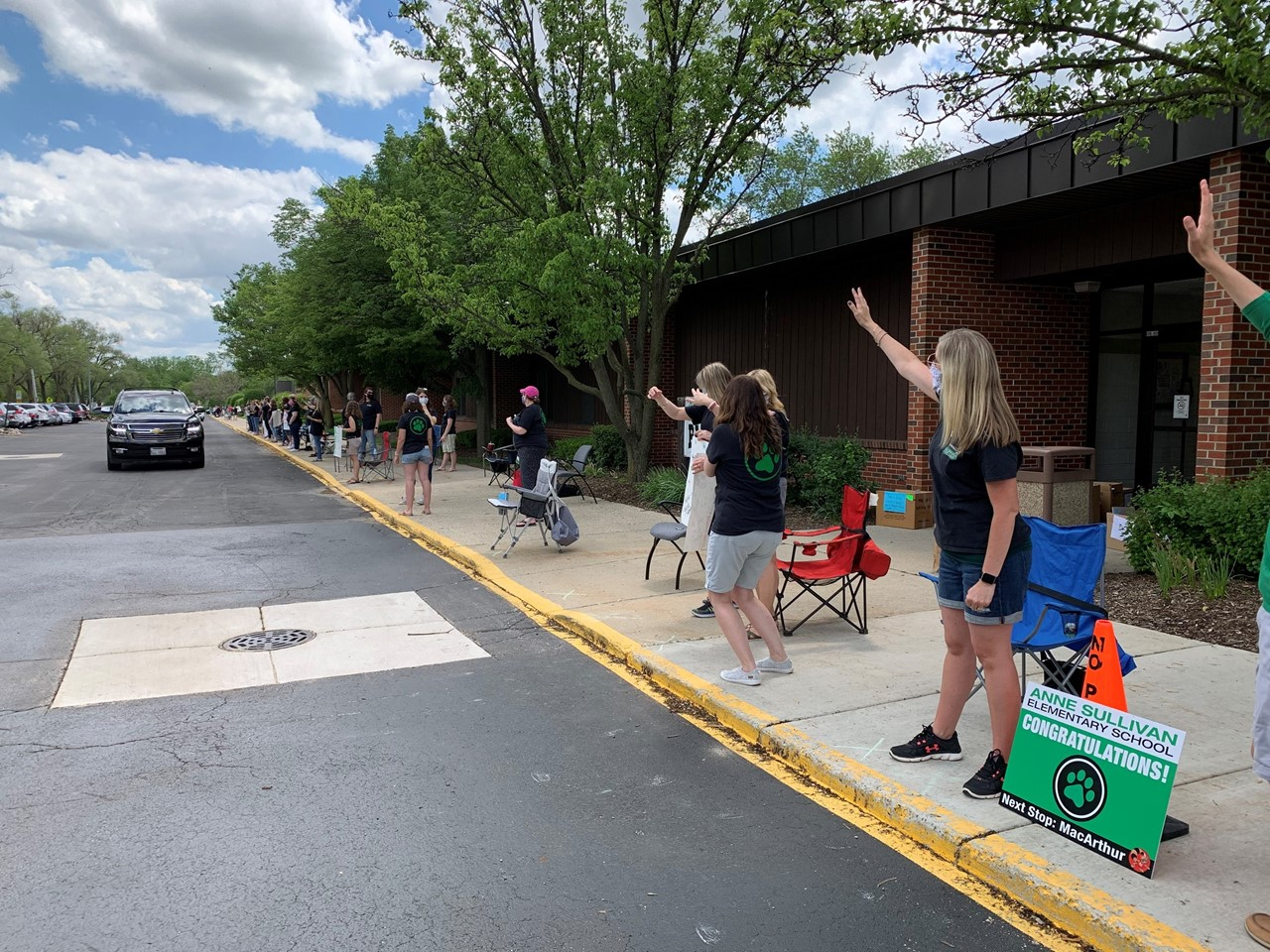 Teachers are standing on the sidewalk in front of Anne Sullivan elementary school waving as cars from students and families are driving by to end the school year. This is a graduation and goodbye parade for students after our distance learning at home.