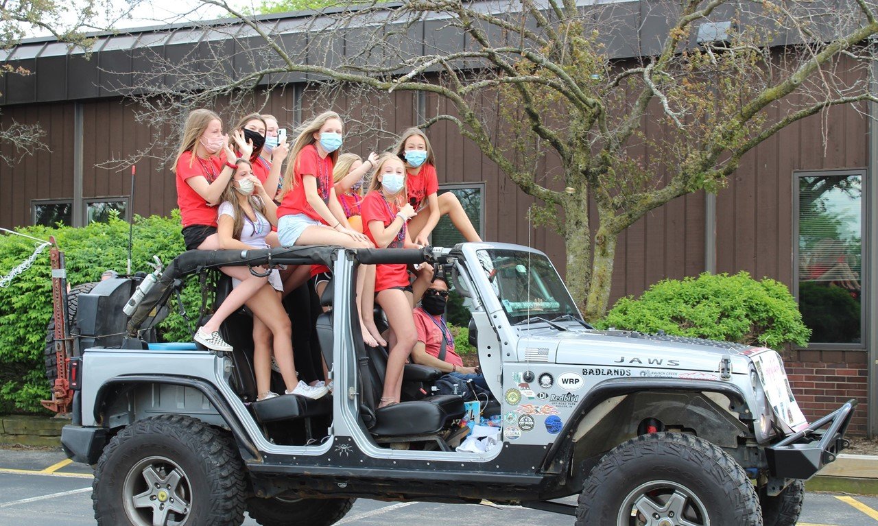 Girls standing in a Jeep as they drive through for the end of year parade.