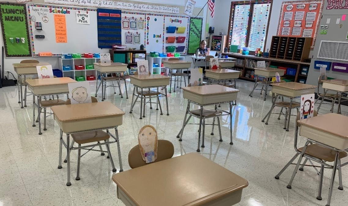 Pictures of students (artwork created by students) are taped onto chairs. The artwork is a drawing of themselves and it looks like they are sitting in their chairs. This artwork is in Mrs. MacTavish's class (4th grade).